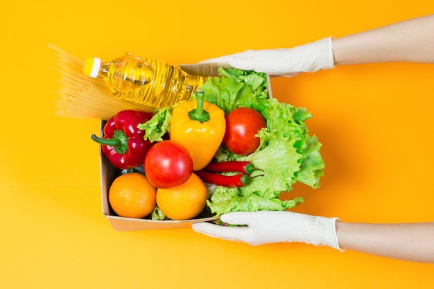Weibliche hände in medizinischen handschuhen halten einen karton mit lebensmitteln, sonnenblumenöl, pfeffer, chili, orangen, tomaten, nudeln, isoliert über einem orangefarbenen raum