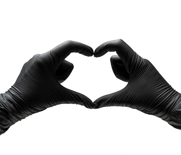 Weibliche hände in medizinischen schutzgummihandschuhen von schwarzer farbe zeigen ein symbol des herzens der liebe.