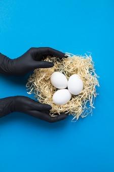 Weibliche hände in schwarzen handschuhen mit weißen hühnereiern in einem nest aus stroh isoliert