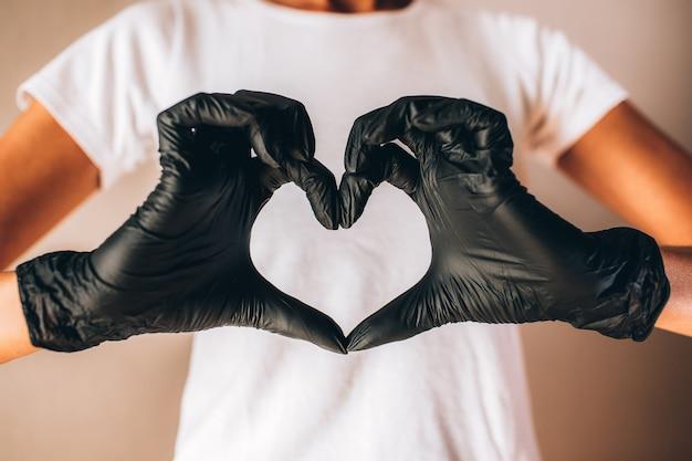 Weibliche hände in schwarzen latexhandschuhen zeigen herzform. junge dünne sonnenbräunefrau im weißen t-shirt und in den schwarzen handschuhen