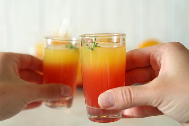 Weibliche hände jubeln mit tequila sunrise, nahaufnahme
