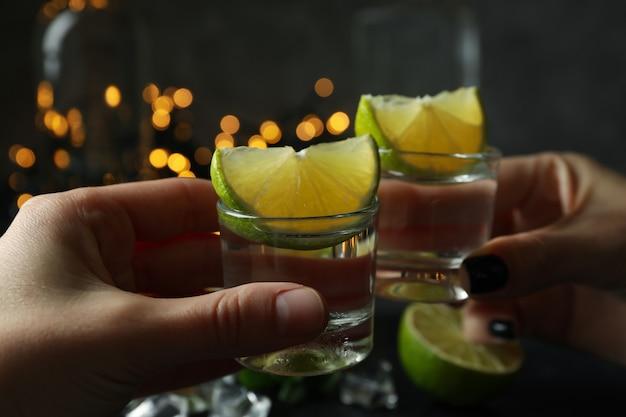 Weibliche hände jubeln mit wodka gegen verschwommene lichter
