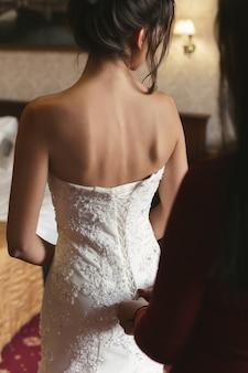 Weibliche hände knöpfen das brautkleid mit einer schönen frisur an die braut