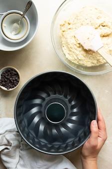 Weibliche hände kochen bundt-kuchen in bundt-zinn-metallpfanne, roher teig für kuchen Premium Fotos