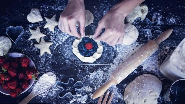 Weibliche hände kochen hausgemachten teigkuchen mit einer füllung aus reifen erdbeeren und saftigen beeren eines geißblattes