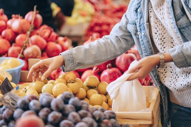 Weibliche hände legen obst und gemüse in baumwollbeutel auf dem lebensmittelmarkt. wiederverwendbare öko-tasche zum einkaufen. nachhaltiger lebensstil. umweltfreundliches konzept.