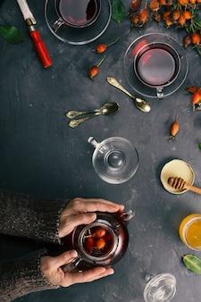 Weibliche hände machen tee mit hagebutten. draufsicht
