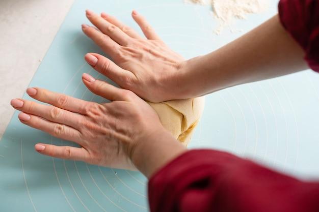 Weibliche hände machen teig an blauer matte