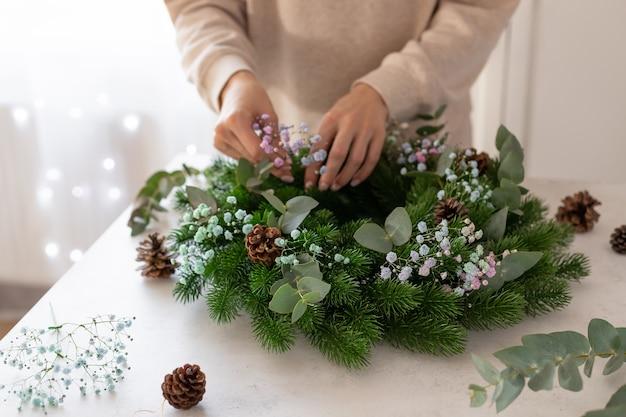 Weibliche hände machen weihnachtskranzweihnachten neujahrsfeier dekoration