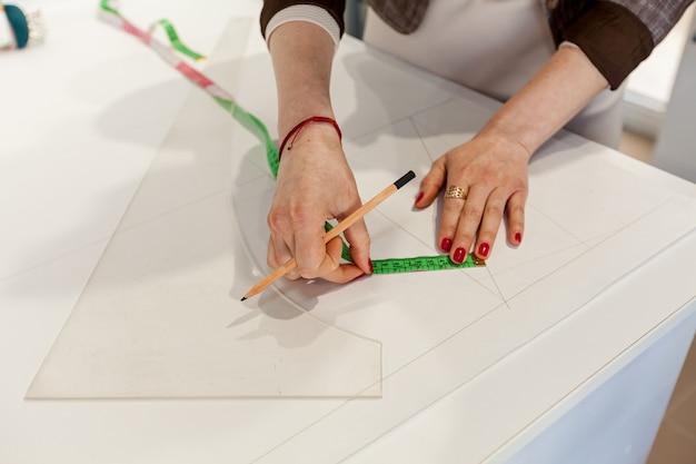 Weibliche hände markieren ein muster auf einem weißen tisch