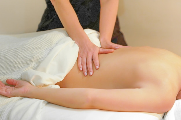 Weibliche hände massieren den rücken einer frau. junge frau, die massage im spa-salon genießt.