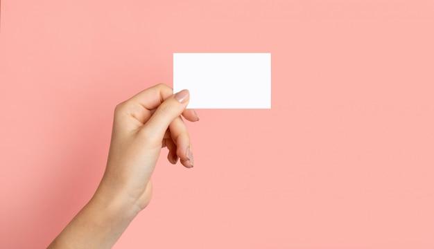 Weibliche hände mit ausschnitt, leeres menü, rabattkarte, visitenkarte auf farbigem rosa schönheitshintergrund mit kopienraum. vorlage für design.