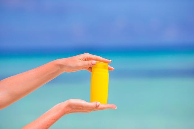 Weibliche hände mit blauem meer der sonnencreme-flasche