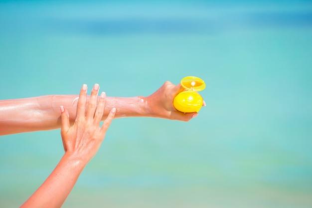 Weibliche hände mit blauem meer des suncream flaschenhintergrundes