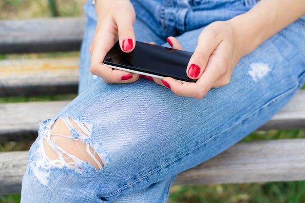 Weibliche hände mit der roten maniküre, die einen handy mit einem touch screen hält