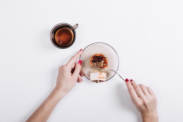 Weibliche hände mit der roten maniküre schnitten ein stück kuchen mit einer gabel