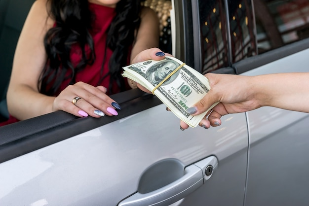 Weibliche hände mit dollarbündel und auto