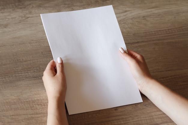 Weibliche hände mit einem blatt papier.