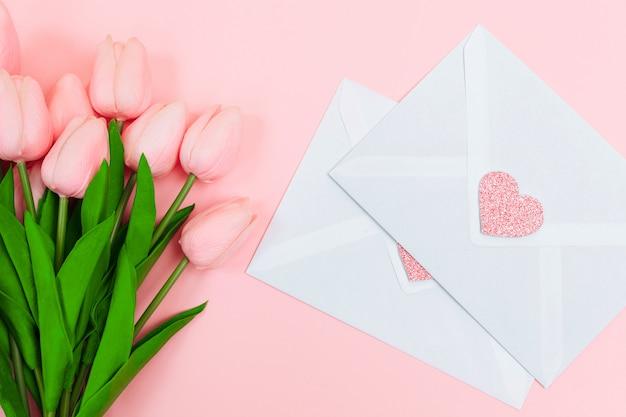 Weibliche hände mit einem blumenstrauß von rosa tulpen und leeren weißen briefumschlägen, auf einem rosa hintergrund. sicht von oben.