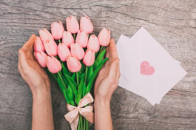 Weibliche hände mit einem blumenstrauß von rosa tulpen und leeren weißen umschlägen für buchstaben, auf einem hölzernen hintergrund.