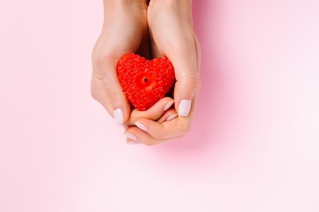 Weibliche hände mit einem roten herzen in form einer kerze auf einem rosa hintergrund. wohltätigkeit und zurückgeben.