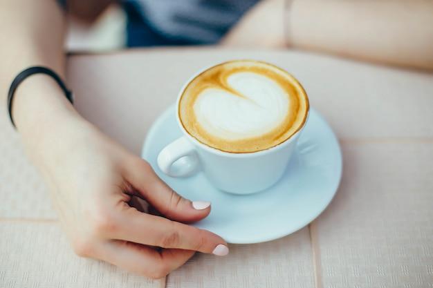 Weibliche hände mit einer cappuccinoschale in einem café