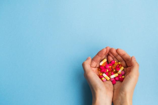 Weibliche hände mit einer handvoll pillen auf blau