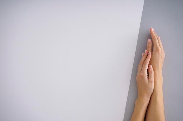 Weibliche hände mit einer schönen maniküre auf einem weißgrauen hintergrund. platz für text.