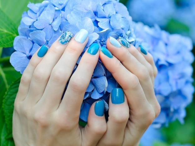 Weibliche hände mit einer schönen maniküre auf einer blauen blume