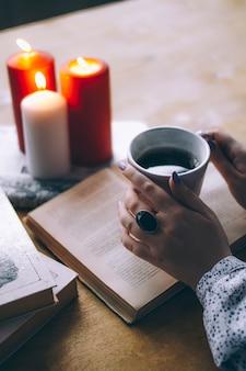 Weibliche hände mit einer tasse kaffee-nahaufnahme von büchern und von kerzen