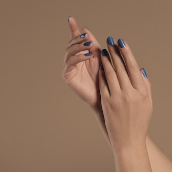 Weibliche hände mit gemalten blauen nägeln auf beigem hintergrund