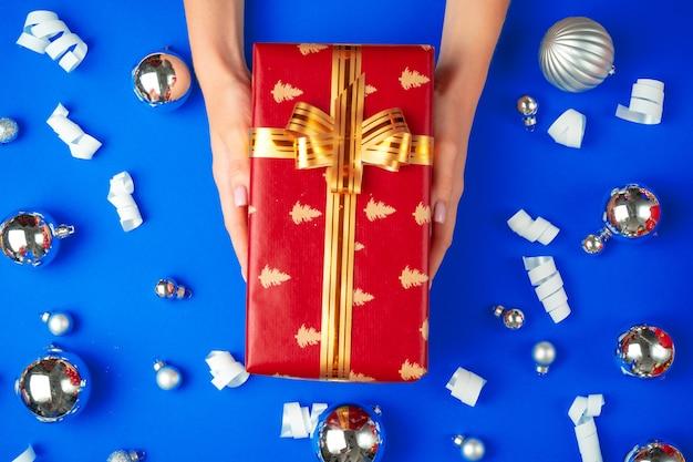 Weibliche hände mit geschenkbox auf einem blauen hintergrund
