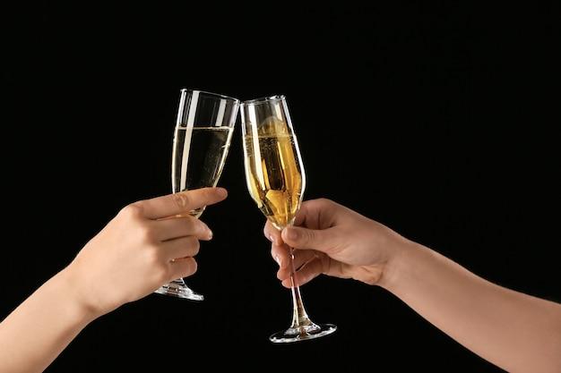 Weibliche hände mit gläsern champagner auf dunklem hintergrund