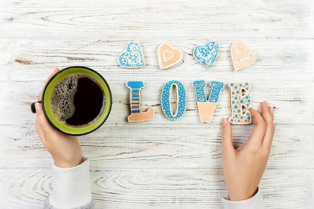 Weibliche hände mit kaffee und herzen formten plätzchen auf holztisch