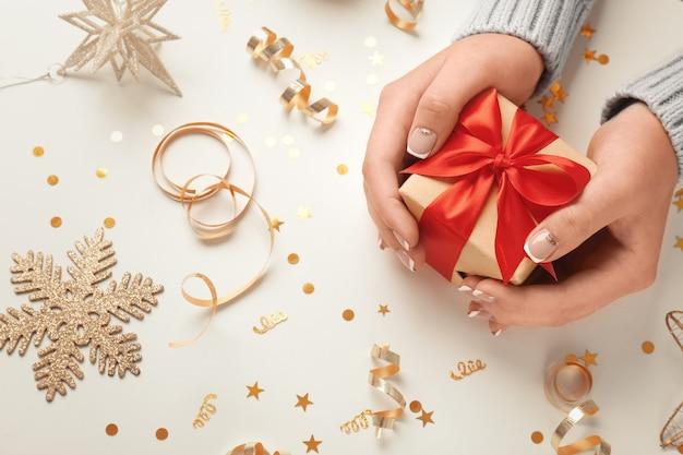 Weibliche hände mit kleiner geschenkbox und weihnachtsschmuck auf hellem hintergrund