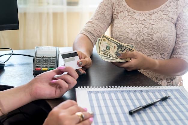 Weibliche hände mit kreditkarte, terminal für zahlung und dollar