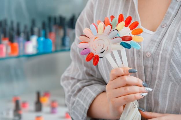 Weibliche hände mit künstlichen acrylnägeln nehmen neue lackfarbe für das maniküre-design-sortiment von nagellacken zum färben von nägeln im schönheitssalon auf
