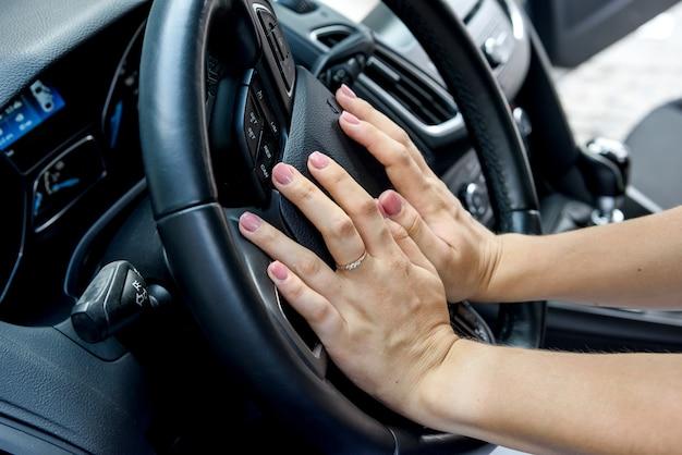Weibliche hände mit lenkrad schließen. frau, die auto fährt und festes autolenkrad hält