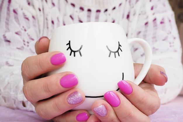 Weibliche hände mit lila maniküre, die einen becher hält