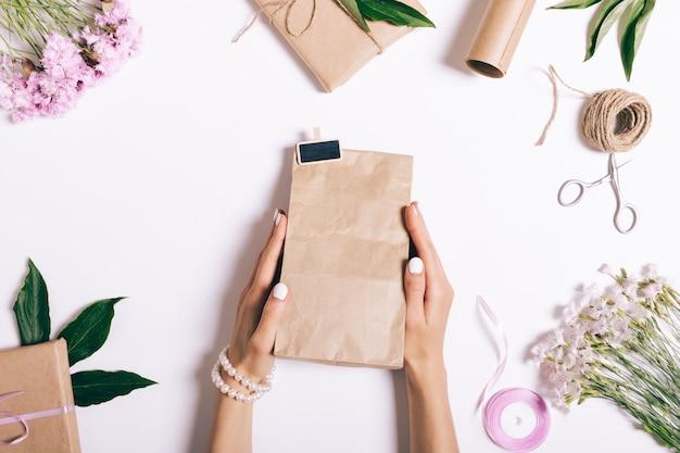 Weibliche hände mit maniküre-packgeschenken auf weiß