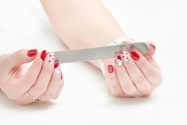 Weibliche hände mit maniküre, roter nagellack, nagelfeile in der hand.
