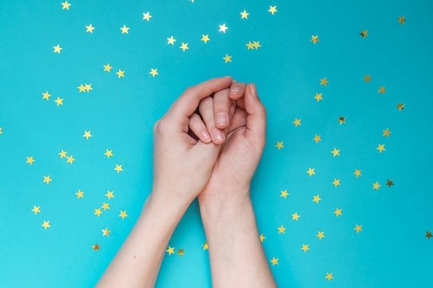 Weibliche hände mit nackter maniküre auf blauer wand mit verstreuten goldenen sternen. festliche mauer. konzept der natürlichkeit.