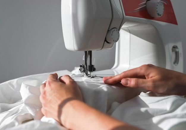 Weibliche hände mit natürlichem baumwolltuch, die an der nähmaschine arbeiten, kleines nähgeschäftskonzept