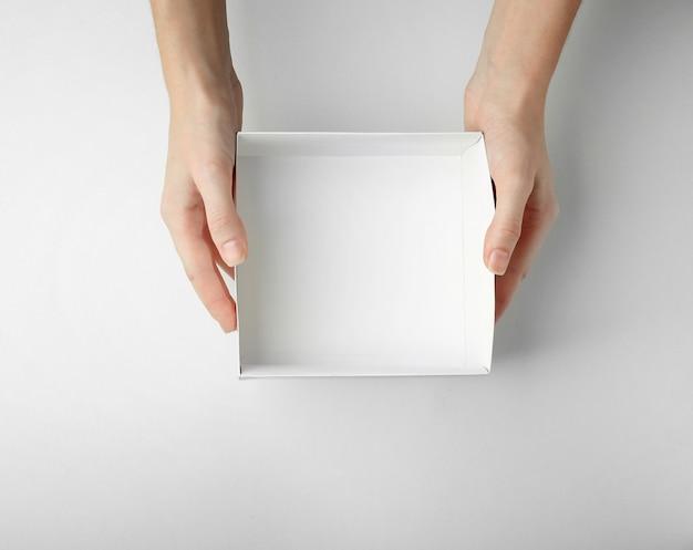Weibliche hände mit offener box auf weißer oberfläche