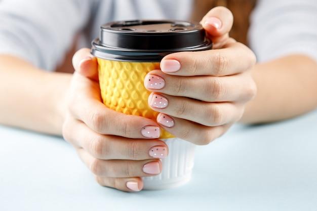 Weibliche hände mit rosa nageldesign, das gelbe tasse hält.