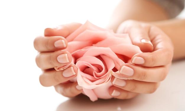 Weibliche hände mit rosa rose. weiblichkeitskonzept