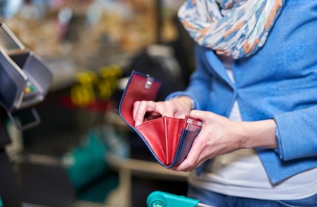 Weibliche hände mit rotem geldbeutel