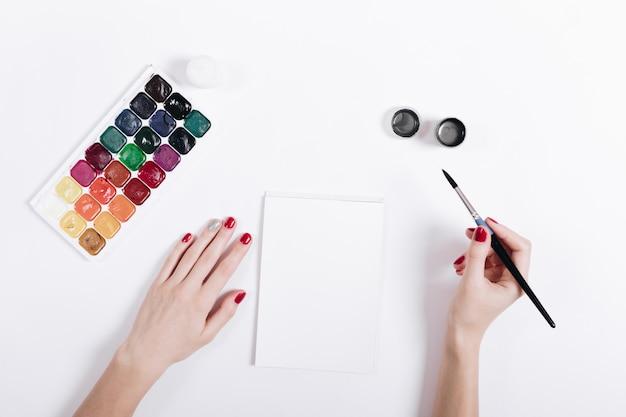 Weibliche hände mit rotem nagellack malten aquarelle in einem notizbuch