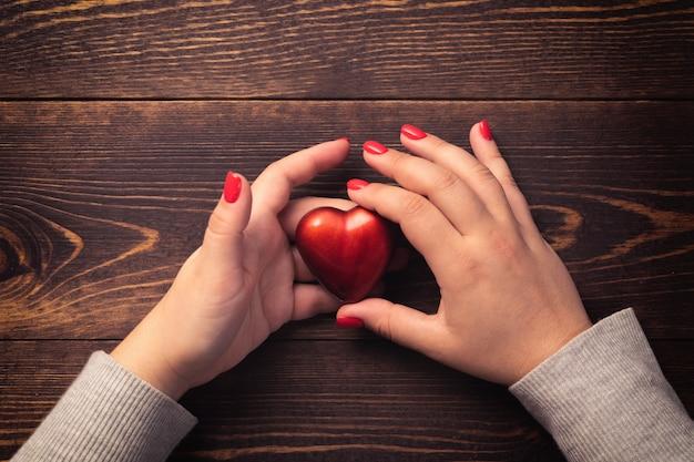 Weibliche hände mit roten nägeln, die herz auf hölzernem hintergrund halten.