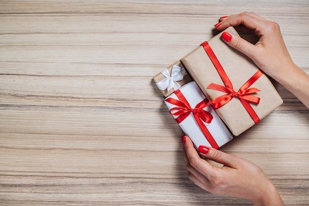 Weibliche hände mit roten polierten nägeln, die bündel von geschenkboxen auf hölzernem hintergrund halten